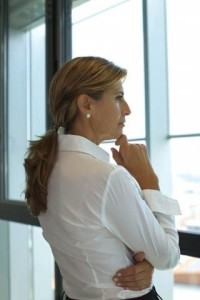 Businesswoman looking out of window with hand under chin --- Image by © Antoine Arraou/PhotoAlto/Corbis